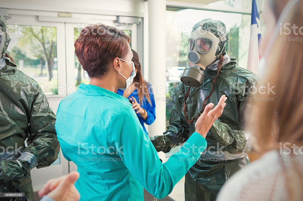 Hazmat team examining office workers after contagious outbreak stock photo