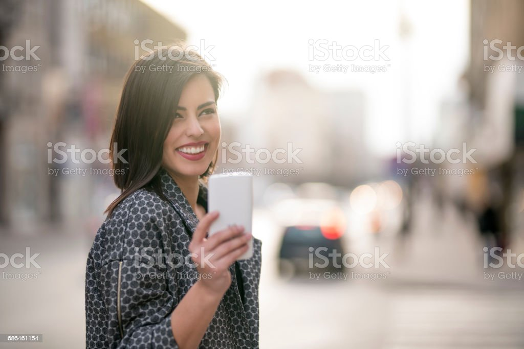 Portrait of a beautiful young woman standing on the city street and...