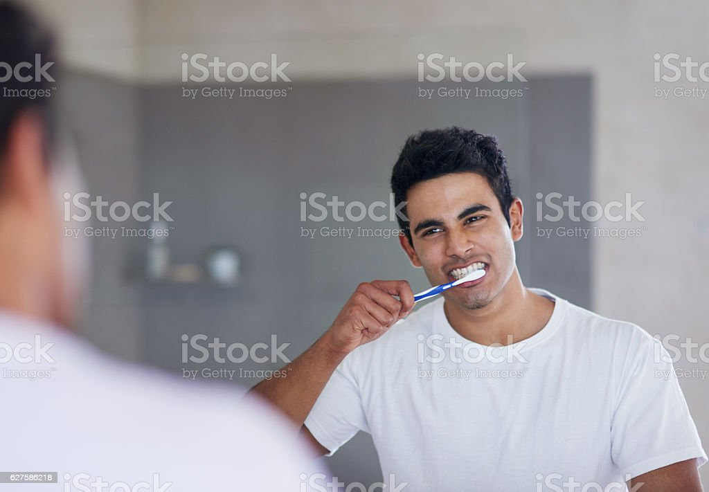 He brushes twice daily for optimal oral health stock photo