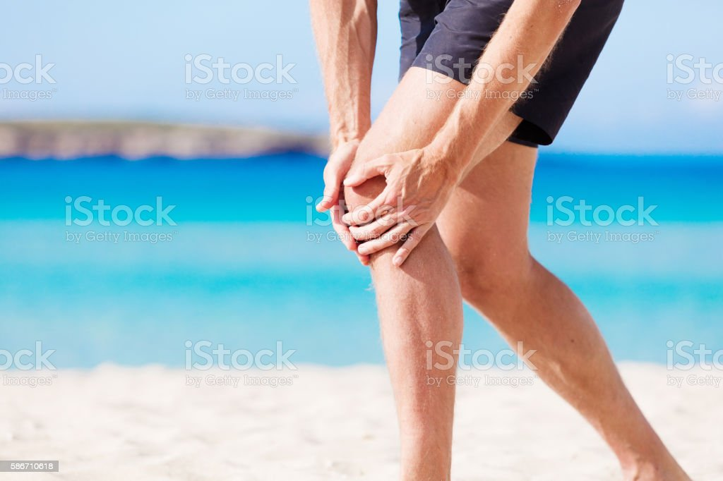 He is having severe knee pain at the beach stock photo