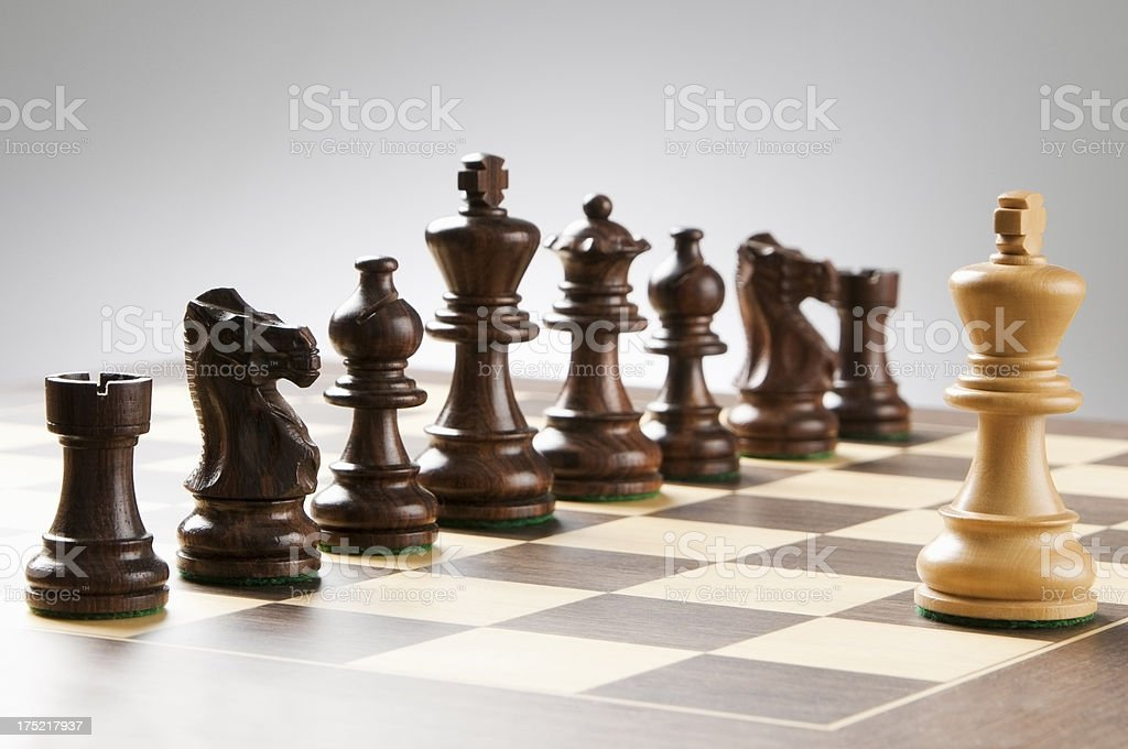 he king chess piece stands surrounded by opposing side stock photo