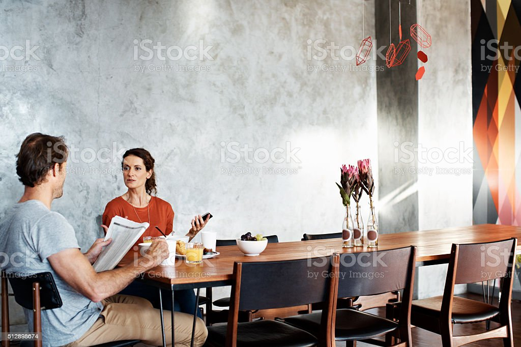 He likes the paper and she prefers the internet stock photo
