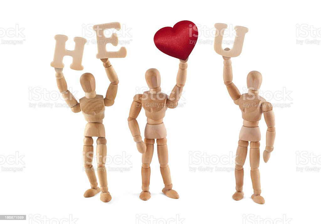 He loves you - wooden mannequin holding words and heart stock photo