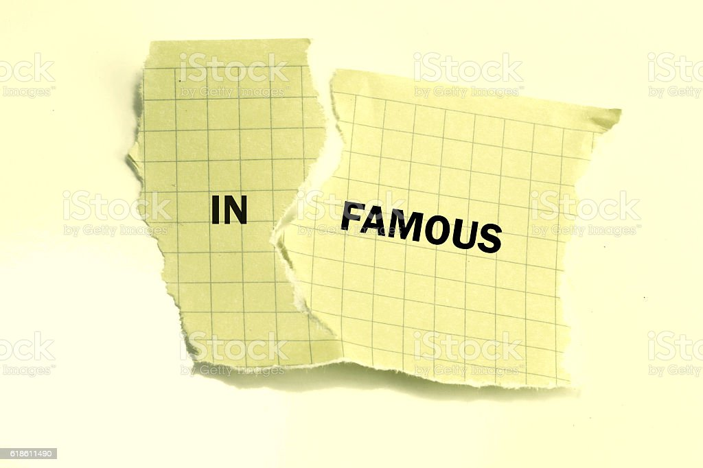 he word infamous changed to famous on torn paper stock photo