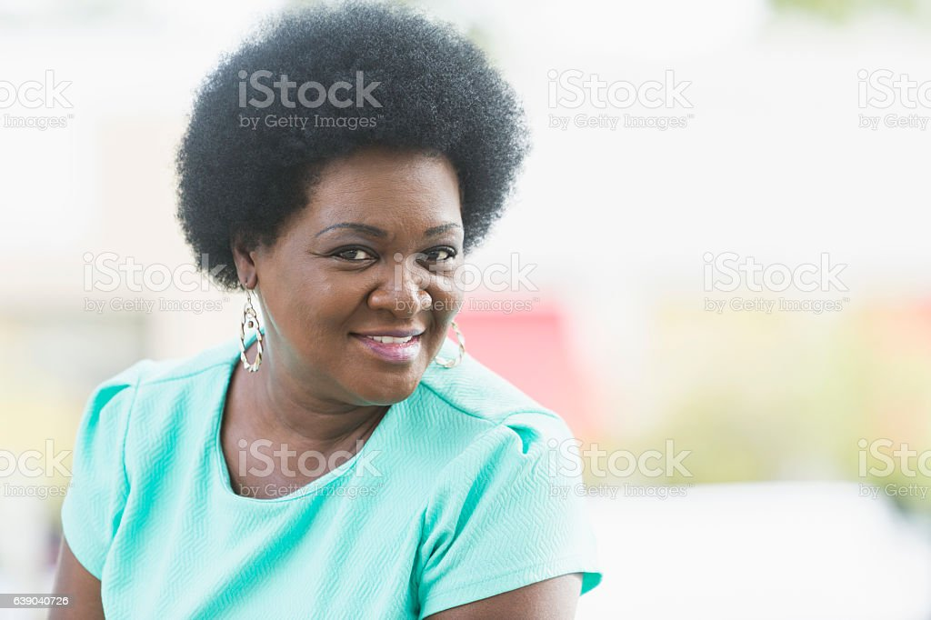 Head and shoulders of mature black woman with afro stock photo