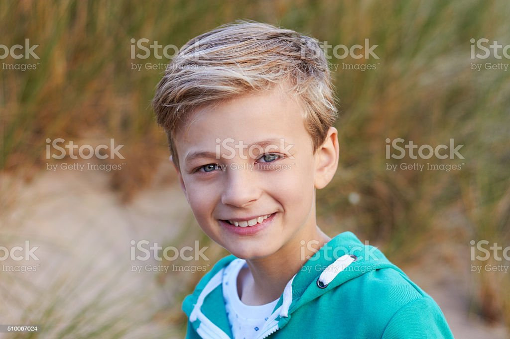 Head And Shoulders Portrait Of Boy By Sand Dunes stock photo