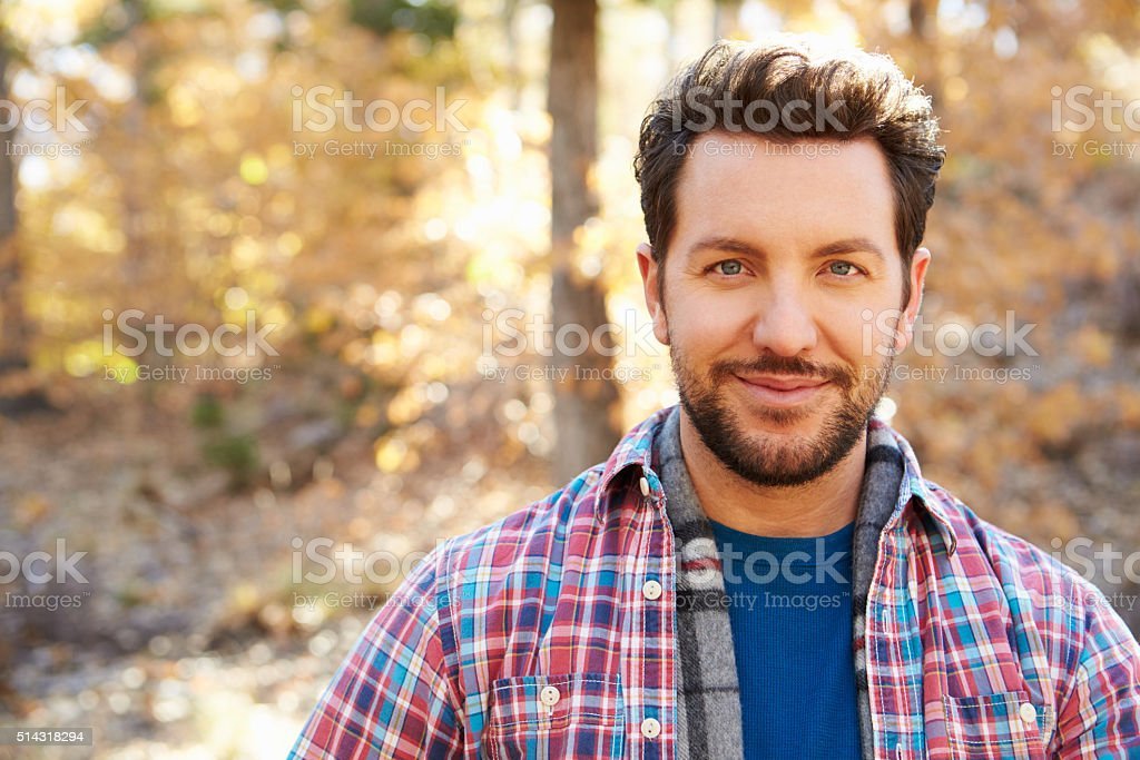 Head And Shoulders Portrait Of Man In Autumn Woodland stock photo