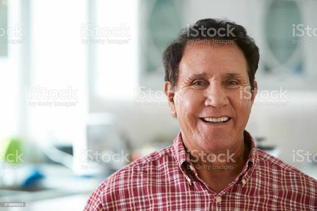 Head And Shoulders Portrait Of Senior Hispanic Man At Home stock photo