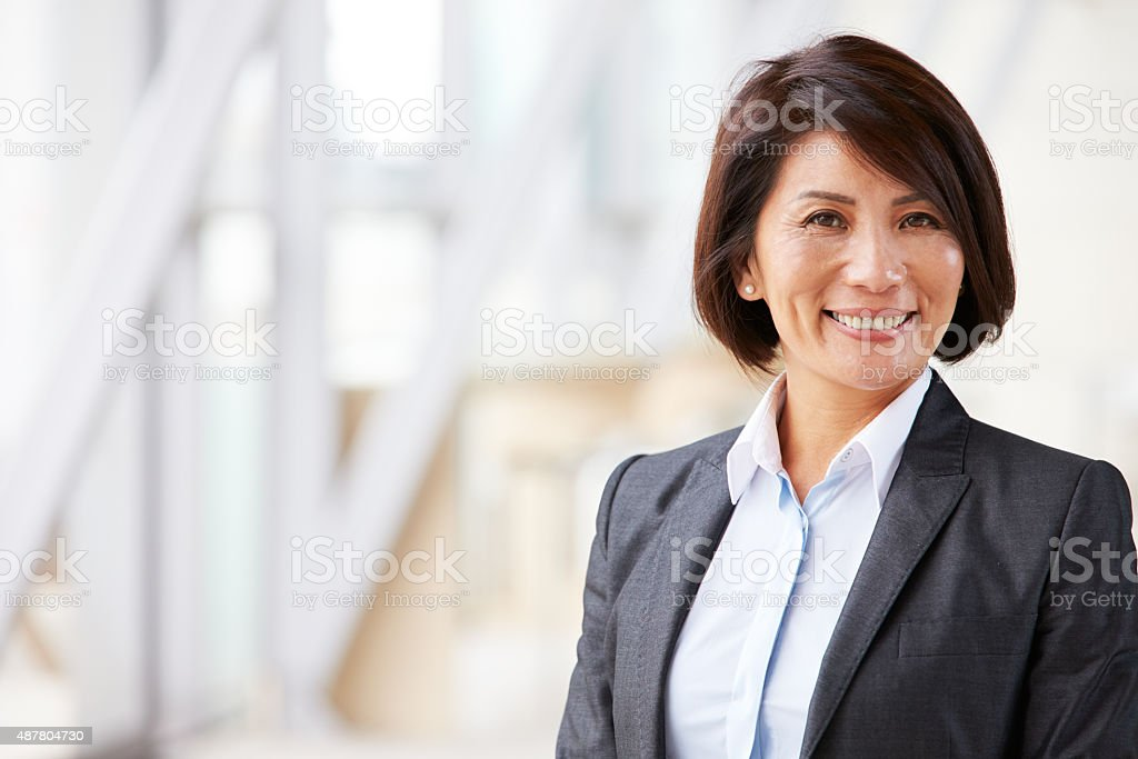 Head and shoulders portrait of smiling Asian businesswoman stock photo