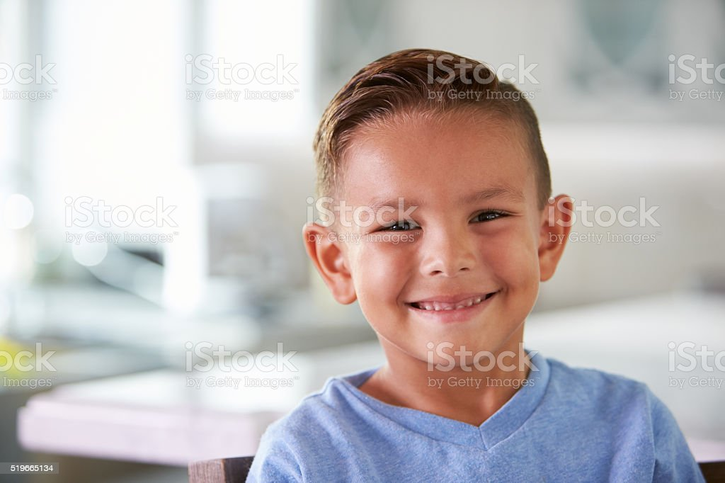 Head And Shoulders Portrait Of Smiling Hispanic Boy At Home stock photo