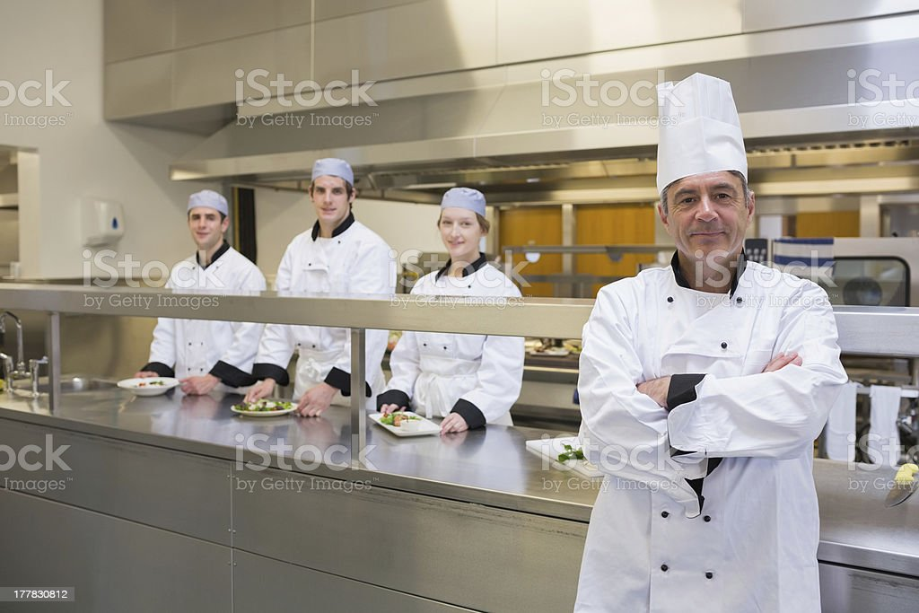 Head chef standing with team behind him stock photo