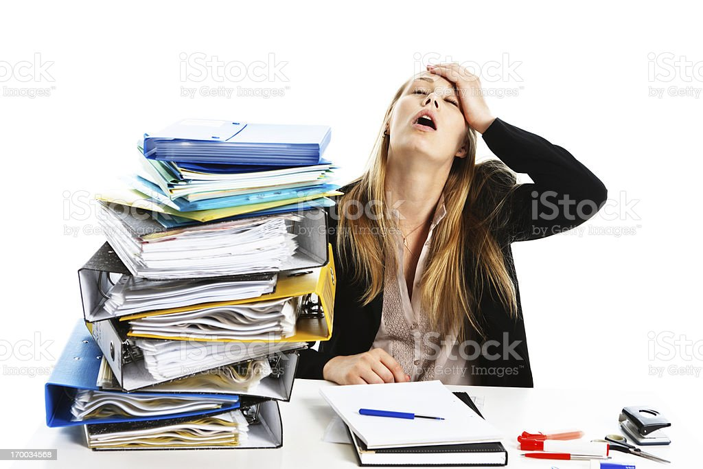 Head in hands despairing young businesswoman with huge workpile royalty-free stock photo