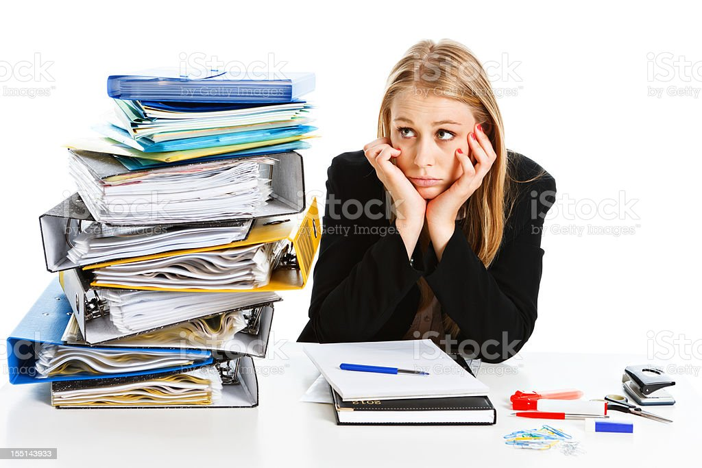 Head in hands sad young businesswoman looks at towering files royalty-free stock photo