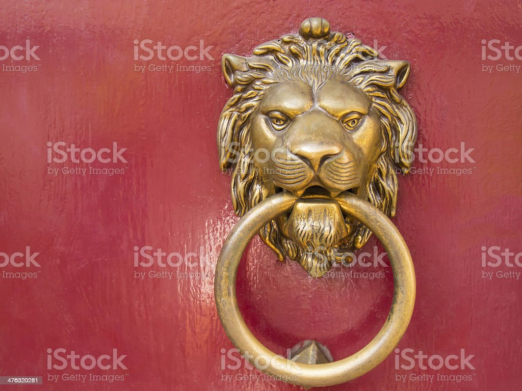 head lion knocks on the red door royalty-free stock photo