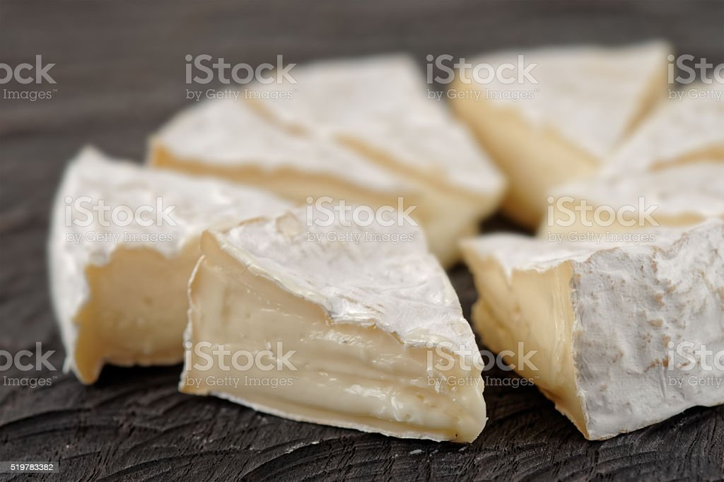 Head of brie cheese cut in pieces stock photo