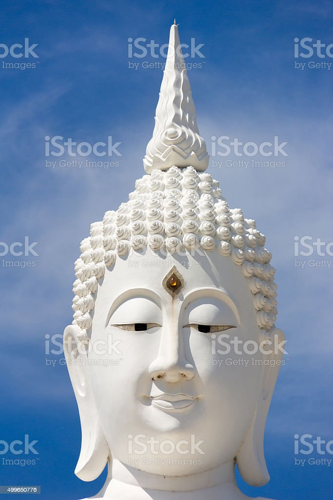 head of white buddha against blue sky stock photo