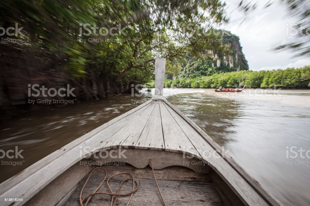 Head of wooden boat moving on canal in mangrove forest. Wooden boat ride travel for looking ecology of mangrove forest in Thailand. stock photo