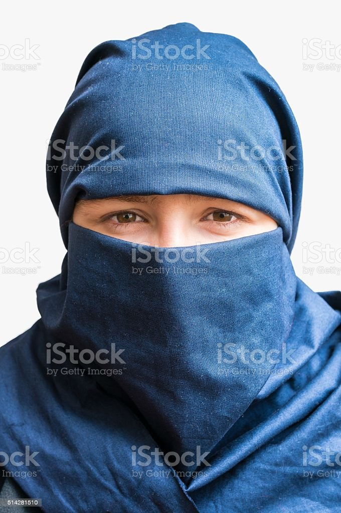 Head of young woman veiled with blue niqab scarf. Isolated. stock photo