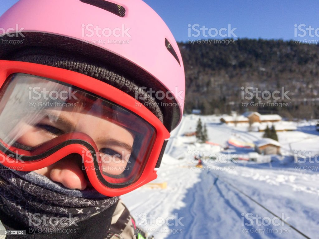 Head shot girl with pink ski helmet and red goggles stock photo