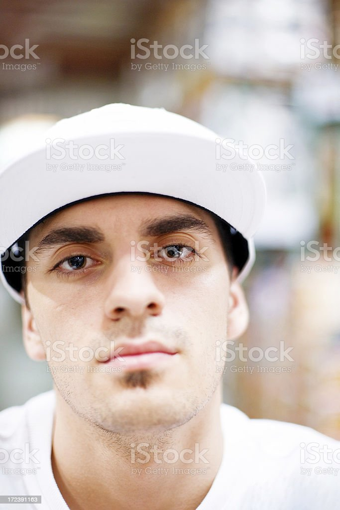 Head shot of man with dilated pupils wearing white sport hat stock photo