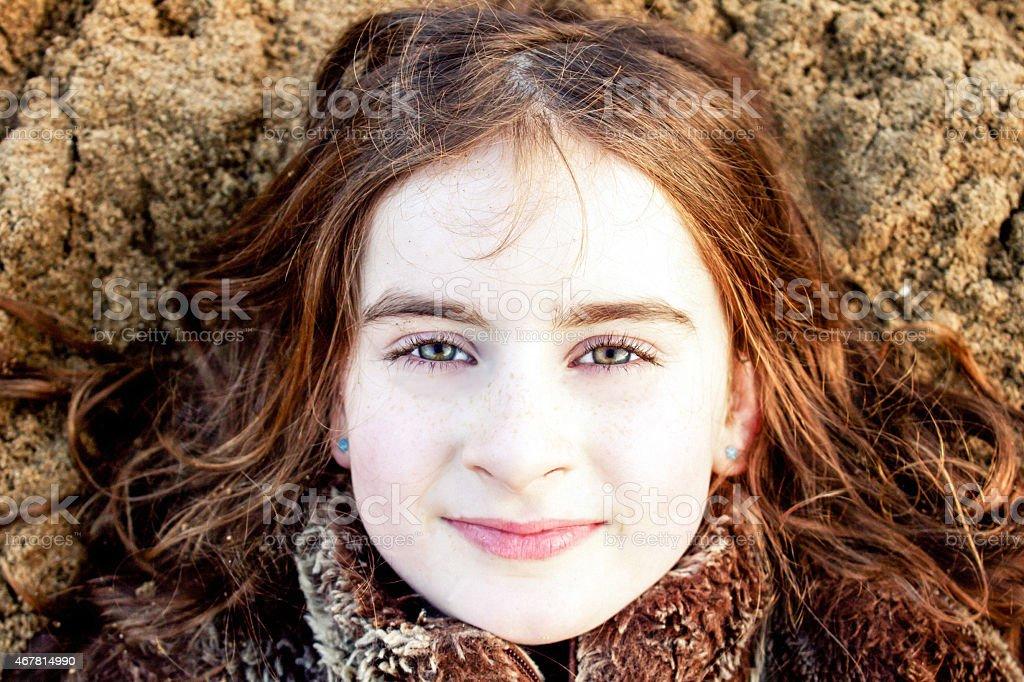 Head shot portrait of young girl lying back on beach stock photo