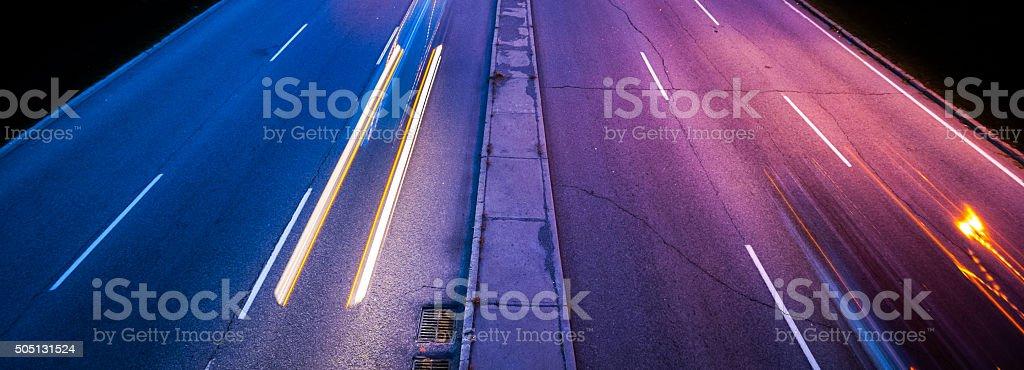 Head & tail light streaks from passing cars illuminate pavement. stock photo
