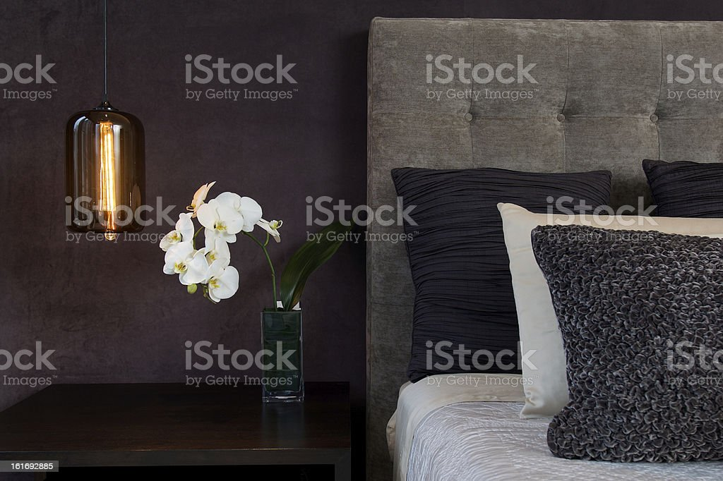 Headboard Detail with Pillows Lamp and Orchid Flowers royalty-free stock photo