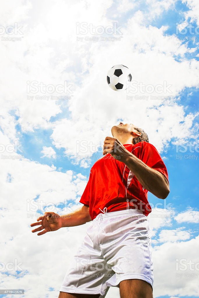 Heading a ball against the sky. royalty-free stock photo