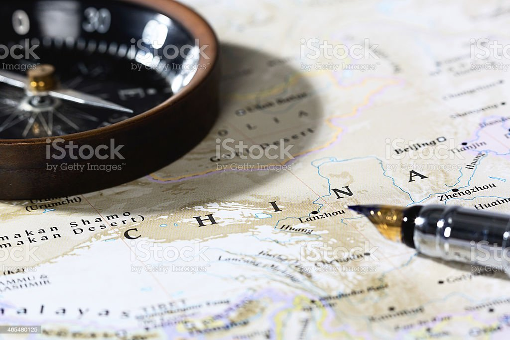 Heading East: map showing China with antique compass and pen stock photo