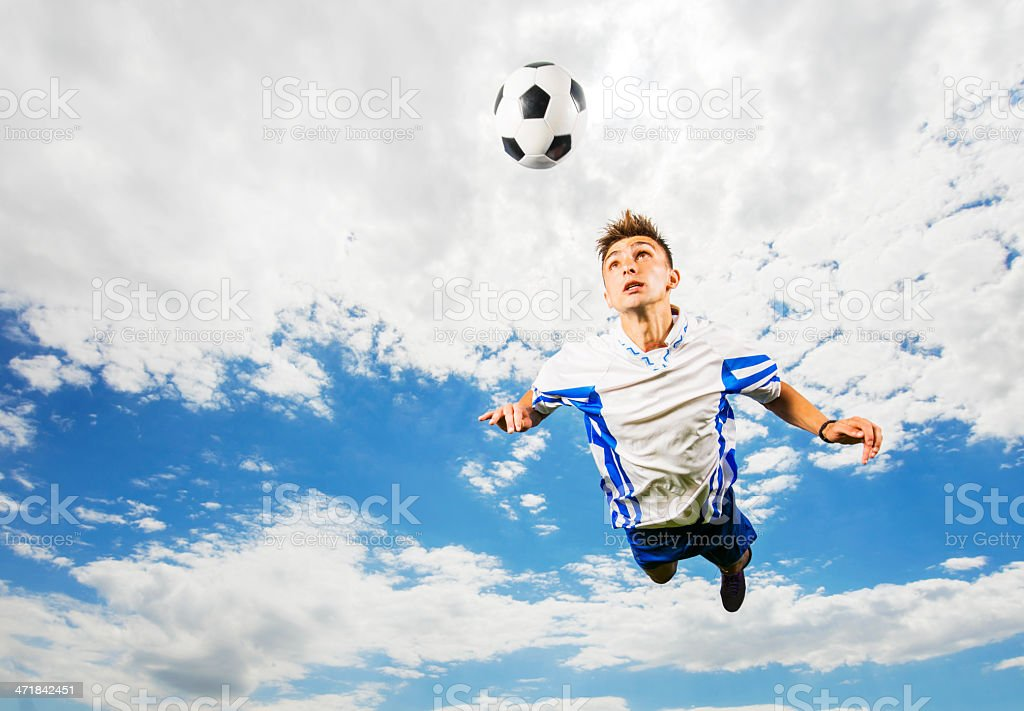 Heading the ball against sky. royalty-free stock photo