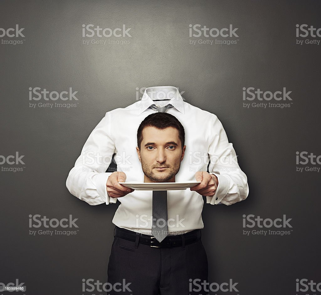 headless man holding head on white plate stock photo