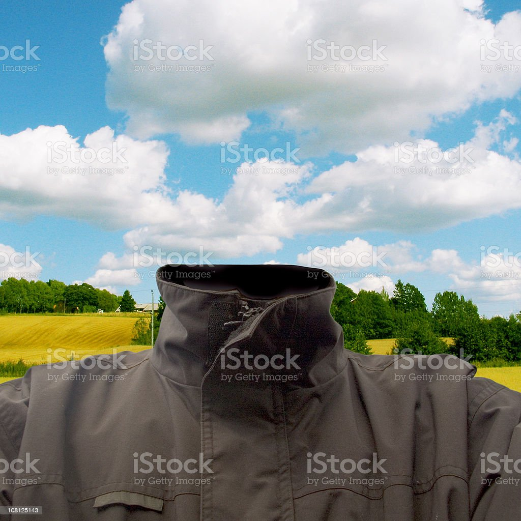 Headless Man Wearing Jacket with Fields in Background and Sky royalty-free stock photo