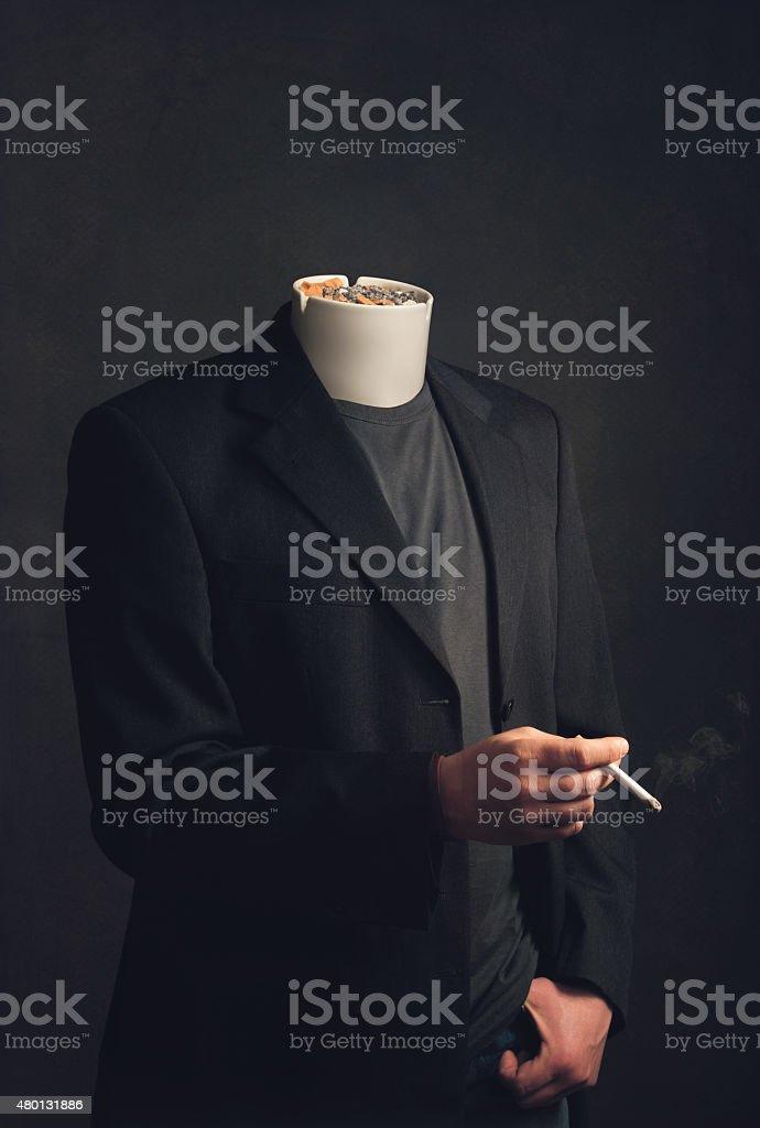 Headless man with ashtray smoking a cigarette stock photo