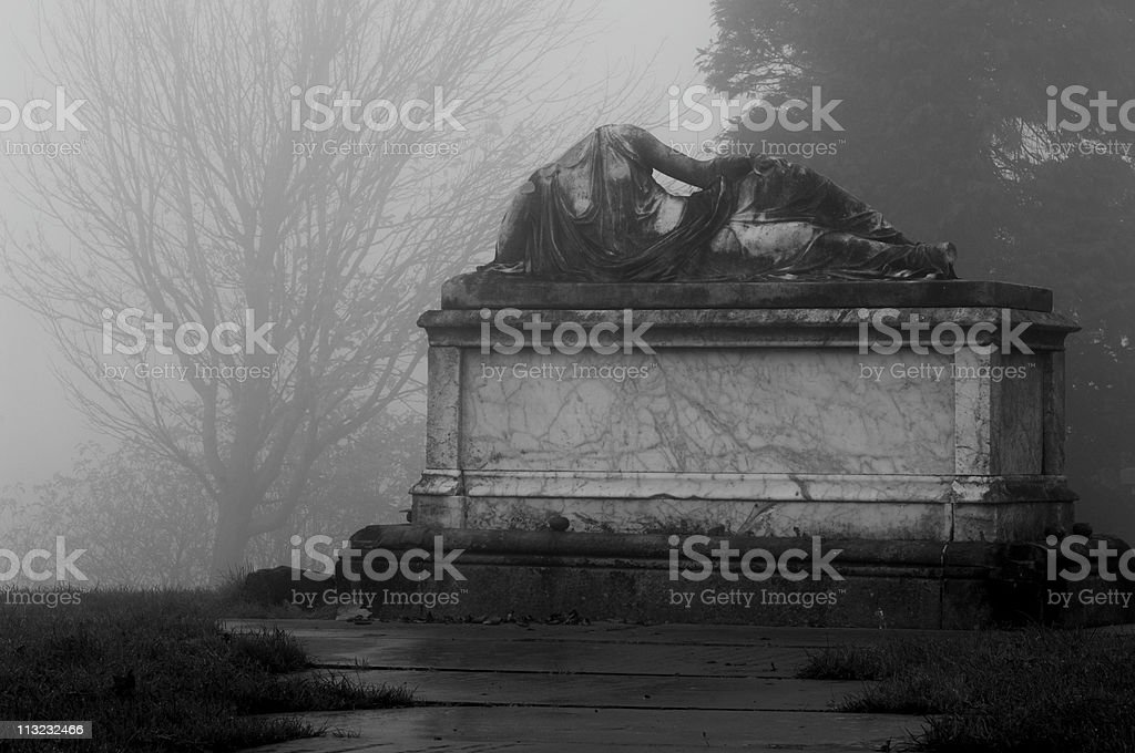 headless statue in a foggy grave yard black and white royalty-free stock photo