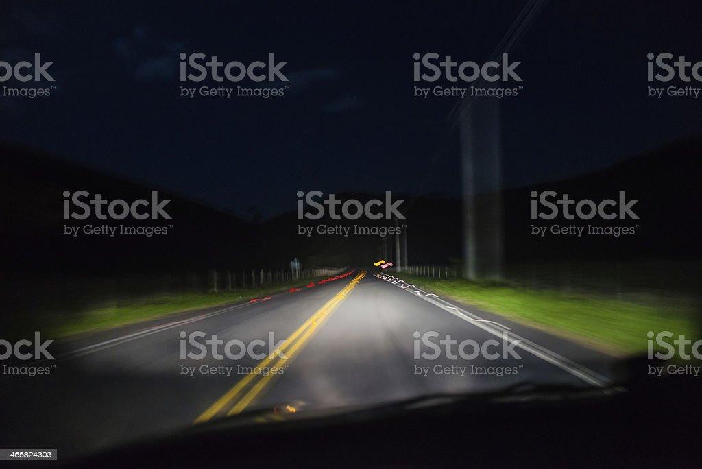 Headlights lighting road at night stock photo