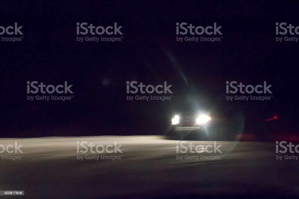 Headlights of a car driving in the dark on snow stock photo