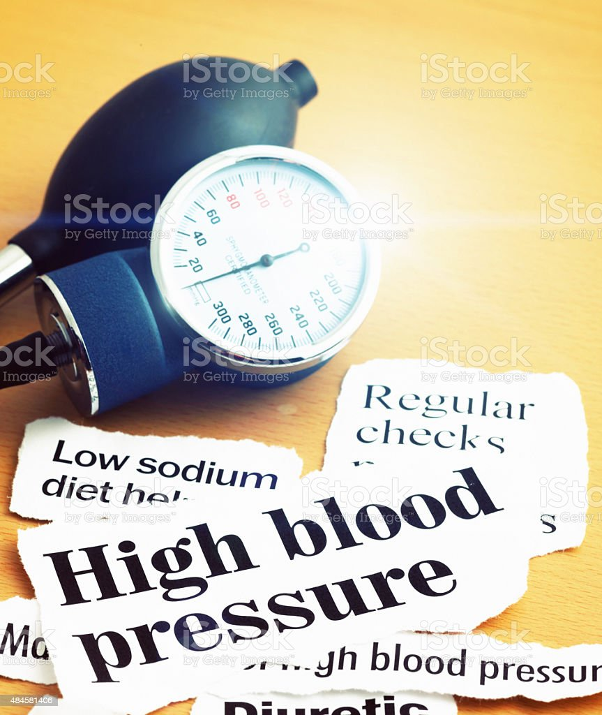 Headlines on high blood pressure with flare on pressure gauge stock photo