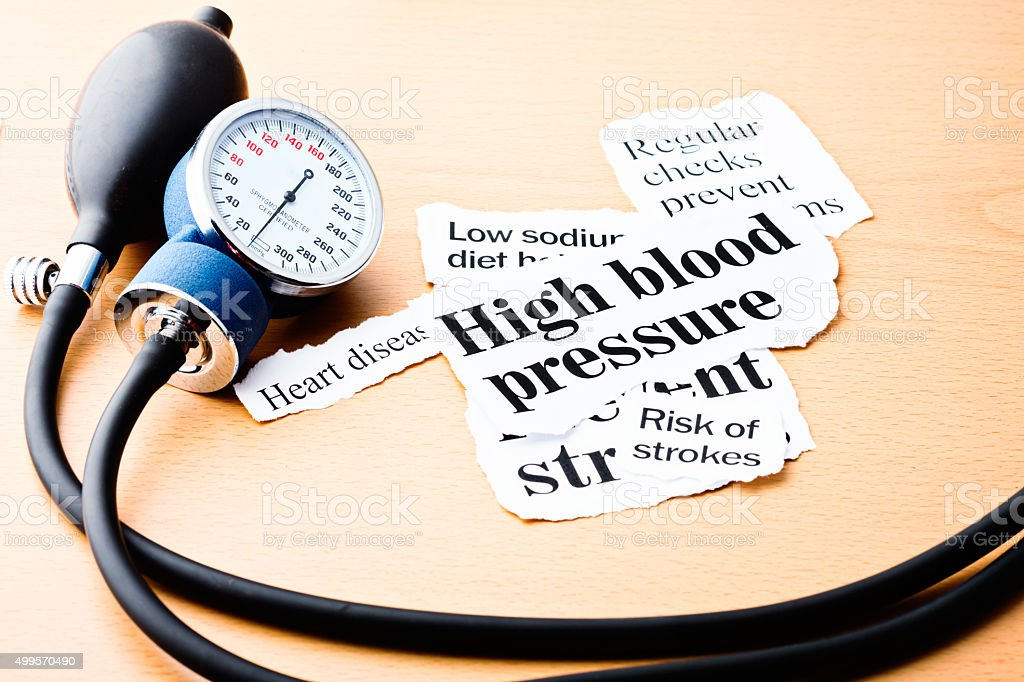 Headlines on hypertension with blood pressure meter stock photo