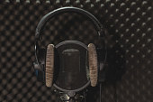 Headphone and microphone recording studio on a black background.
