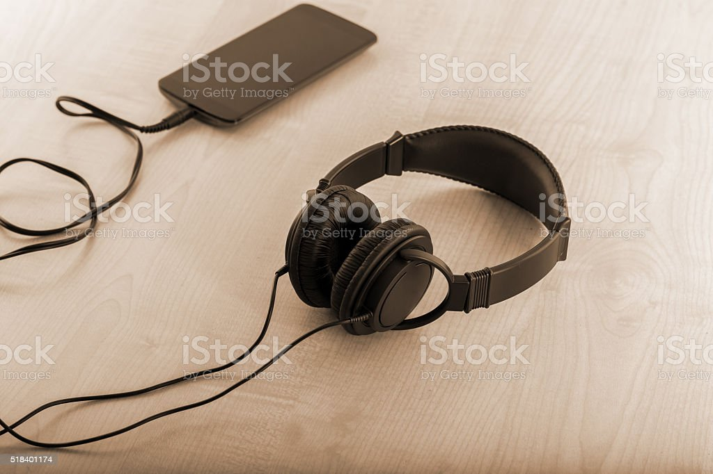 Headphone Connected To Smartphone- Listen To The Music Concept stock photo