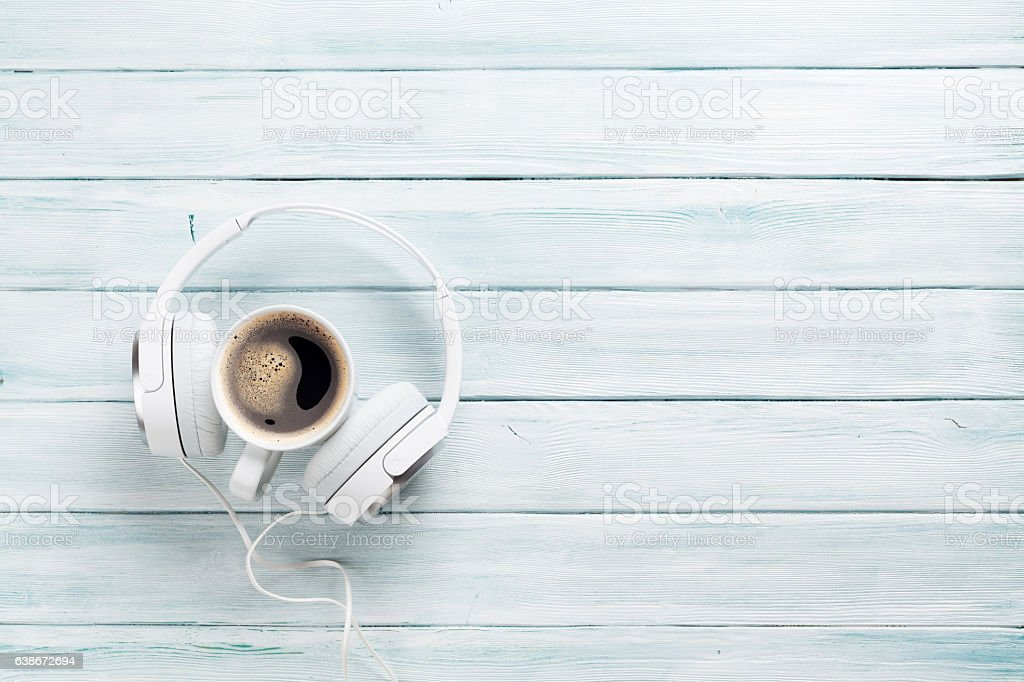 Headphones and coffee cup on wooden table stock photo