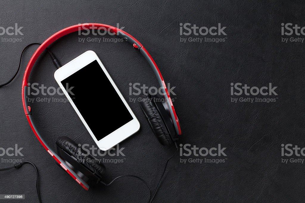 Headphones and smartphone on desk stock photo