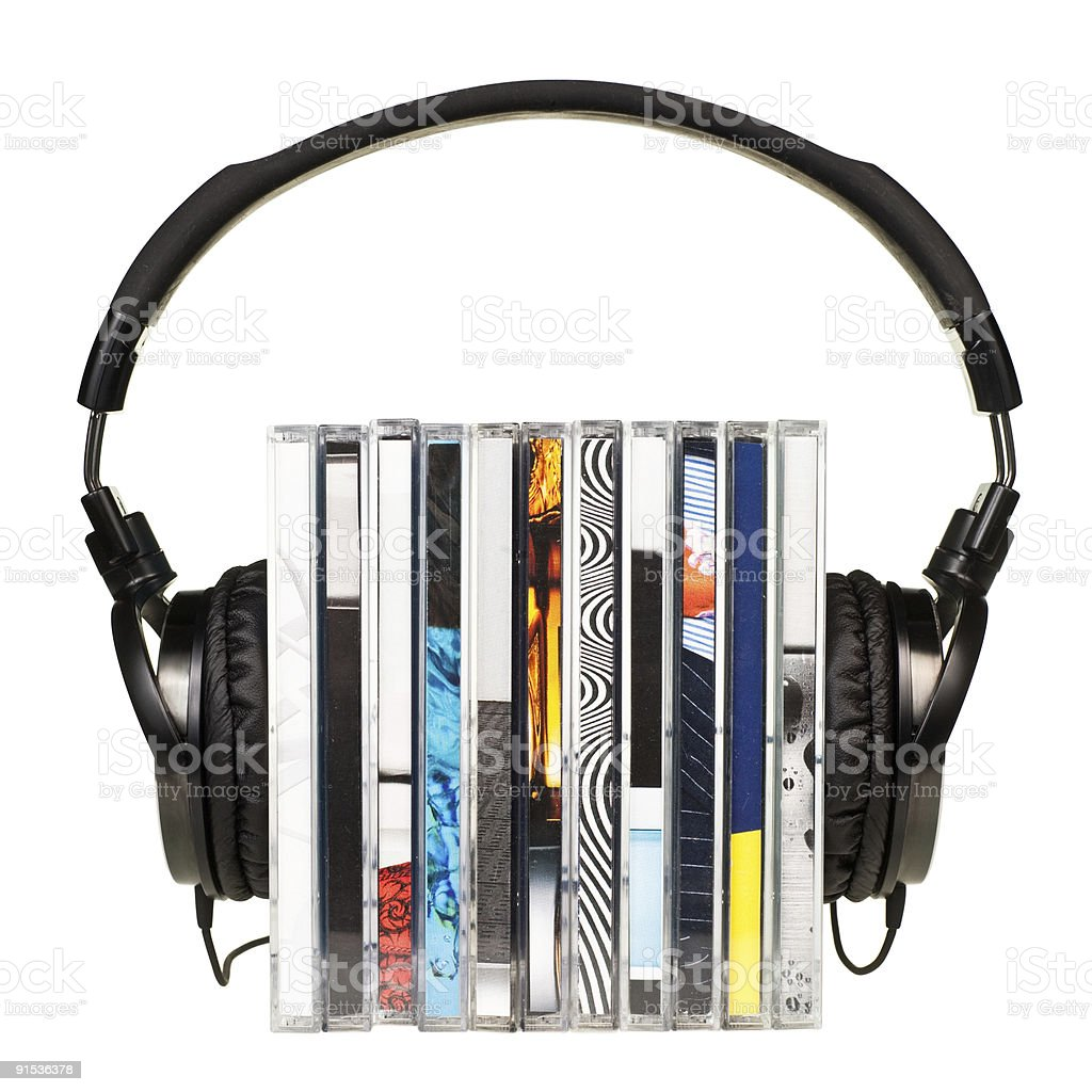 Headphones holding a stack of CDs on white background stock photo