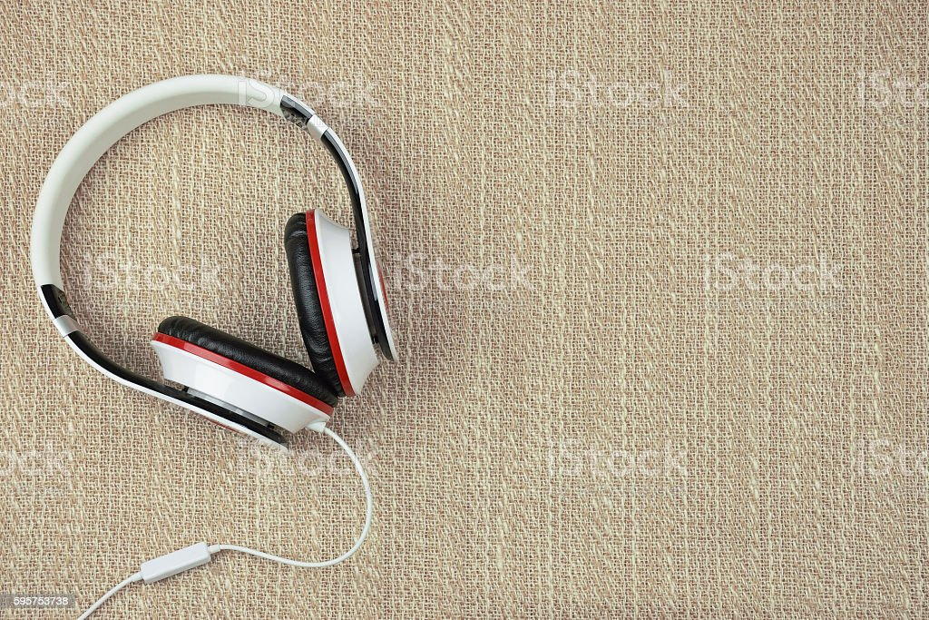 Headphones on a rough fabric background. Listen to music. stock photo
