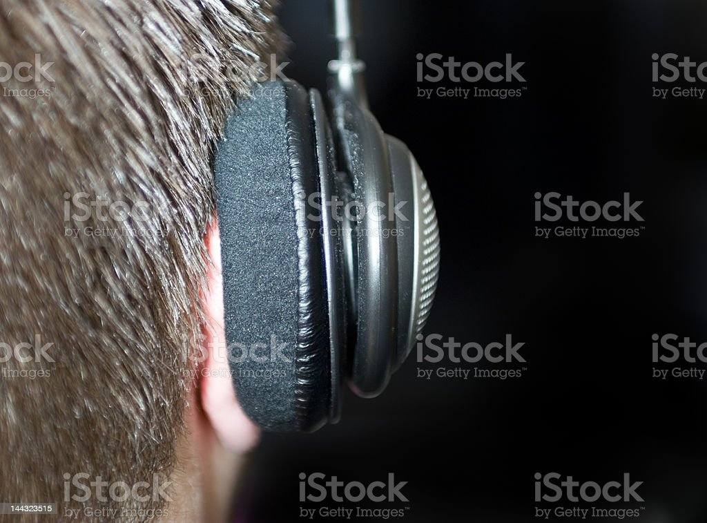 Headphones on man from behind stock photo