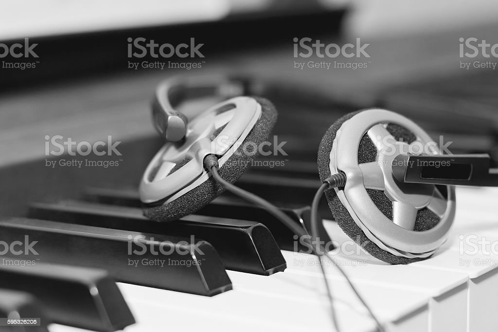 Headphones on piano keyboard stock photo