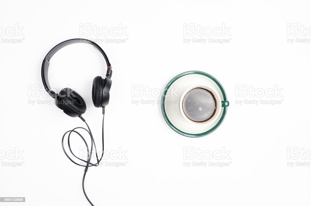 Headphones with mug of coffee on a white background. stock photo