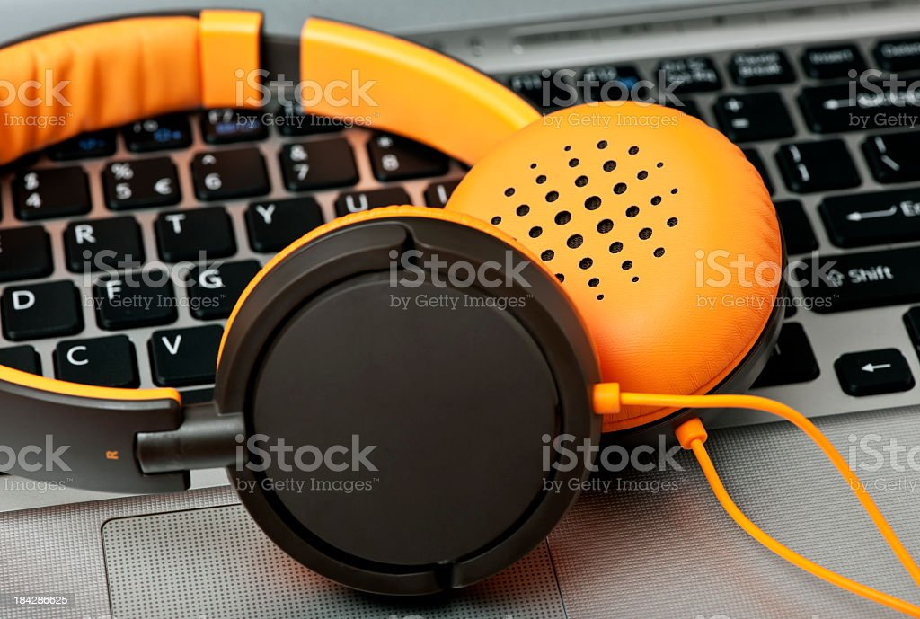 Headphones with orange lining on top of laptop keyboard stock photo