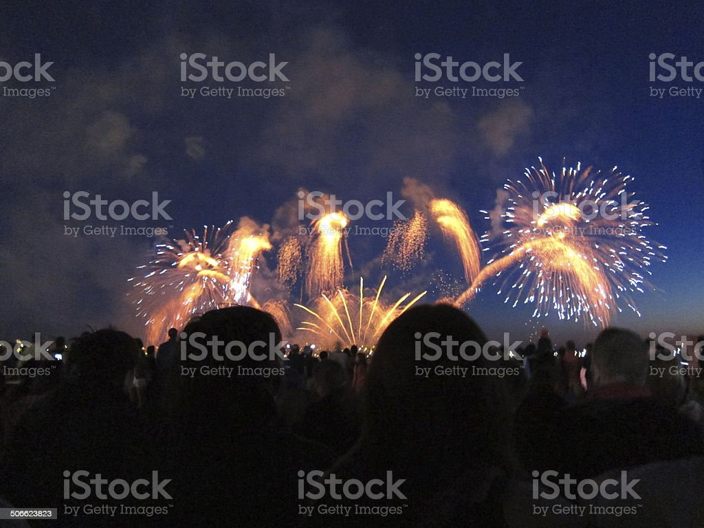 Heads of crowd silhouetted against a bright fireworks display stock photo