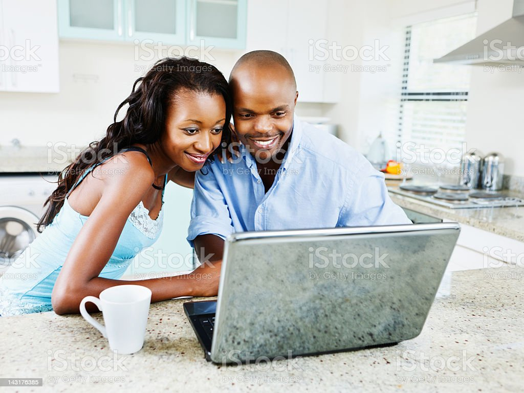 Heads together a young couple share laptop at home royalty-free stock photo
